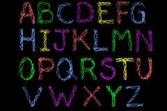 Alfabeto manuscrito coloreado de la tiza en la pizarra Foto de archivo libre de regalías