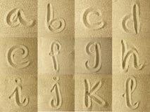 Alfabeto manuscrito en la arena Foto de archivo