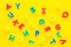 Alfabeto para el concepto de los niños Letras inglesas en desorden en la opinión superior del fondo amarillo fotografía de archivo