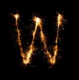 Alfabeto W della luce del fuoco d'artificio della stella filante alla notte Immagine Stock