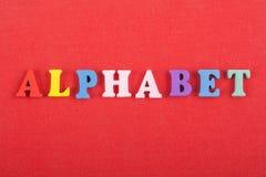 ALFABETord på röd bakgrund som komponeras från träbokstäver för färgrikt abc-alfabetkvarter, kopieringsutrymme för annonstext Royaltyfri Fotografi