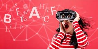 Alfabetten met vrouw die een virtuele werkelijkheidshoofdtelefoon met behulp van Royalty-vrije Stock Foto's