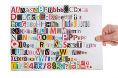 alfabeturklipp hand holdingtidningen Arkivfoton