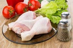 Alface, tomates, alho, sal, pimenta e pés de galinha crus Imagem de Stock Royalty Free