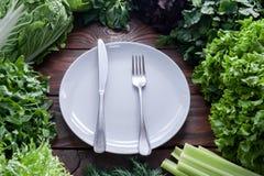 A alface verde, suculenta sae na variedade com a forquilha e na faca em uma opinião superior branca da placa no centro imagens de stock