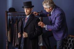 Alfaiate com o cliente na oficina Costurando o terno feito-à-medida foto de stock