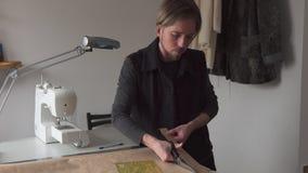 Alfaiate do homem com teste padrão de papel da roupa dos cortes das tesouras na oficina vídeos de arquivo