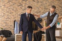 Alfaiate maduro que toma as medidas do cliente na oficina imagem de stock royalty free