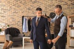 Alfaiate maduro que toma as medidas do cliente na oficina fotos de stock royalty free