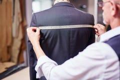 Alfaiate Measuring Garment na oficina imagens de stock