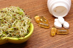 Alfalfa and radish sprouts with tablets supplements, healthy nutrition Royalty Free Stock Photos