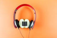 Alfanumerisk äpple och hörlurar Fotografering för Bildbyråer