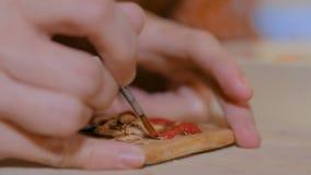 Alfarero de la mujer profesional que pinta el imán de cerámica del recuerdo en taller de la cerámica almacen de video