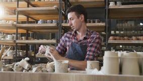 Alfarero de sexo masculino caucásico que hace el casquillo de cerámica en la cerámica almacen de metraje de vídeo