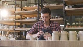 Alfarero de sexo masculino caucásico que hace el florero de cerámica en la cerámica almacen de video