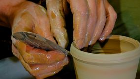 Alfarero profesional que forma la taza con la herramienta especial en taller de la cerámica Fotografía de archivo