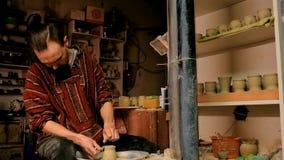 Alfarero profesional que forma la taza con la herramienta especial en taller de la cerámica Foto de archivo libre de regalías