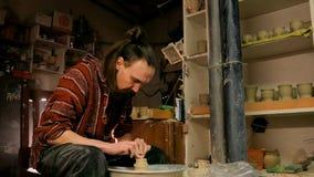 Alfarero profesional que forma la taza con la herramienta especial en taller de la cerámica Foto de archivo