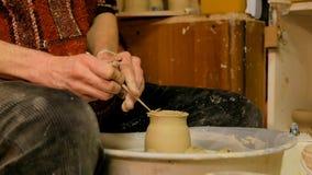 Alfarero profesional que talla la taza con la herramienta especial en taller de la cerámica Foto de archivo