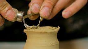 Alfarero profesional que talla la taza con la herramienta especial en taller de la cerámica Foto de archivo libre de regalías