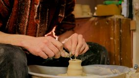 Alfarero profesional que talla la taza con la herramienta especial en taller de la cerámica Imagenes de archivo