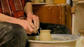 Alfarero profesional que talla la taza con la herramienta especial en taller de la cerámica Fotos de archivo