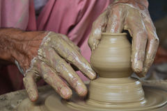 Alfarero que crea el pote en la rueda de la cerámica usando la arcilla Imagenes de archivo