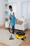 Alfombra de la limpieza de la mujer con el aspirador Imagen de archivo libre de regalías