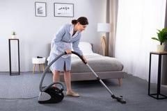 Alfombra de la limpieza del ama de casa con el aspirador fotografía de archivo