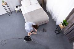 Alfombra de la limpieza del ama de casa con el aspirador imagen de archivo libre de regalías