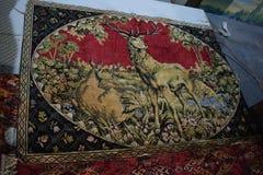 alfombra retra en la pared, representando un ciervo imagenes de archivo