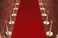 Alfombra roja con la barrera de la cuerda en fondo rojo Fotografía de archivo