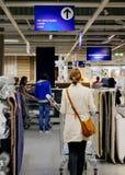 Alfombras de compra de la mujer en la tienda de muebles de Ikea Imágenes de archivo libres de regalías