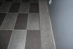 Alfombre las tejas encajadas en una alfombra gris Imagenes de archivo