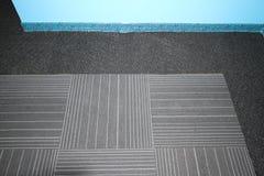 Alfombre las tejas encajadas en una alfombra negra Imagen de archivo