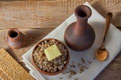 alforfón cocinado con una rebanada de mantequilla servida con las patatas a la inglesa del centeno en la tabla de madera fotos de archivo libres de regalías