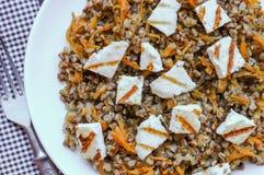 Alforfón con la zanahoria y el queso tajado del adygei Fotografía de archivo