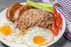 Alforfón con las salchichas, los huevos revueltos, los tomates y los pepinos fritos Imagenes de archivo