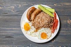 Alforfón con las salchichas, los huevos revueltos, los tomates y los pepinos fritos Fotografía de archivo