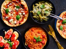 Italian vegetarian platter-pasta,bruschetta and pizza. Alfredo cheese pasta made from Penne pasta with white sauce and cheese.Tomato spaghetti,garlic bread royalty free stock image