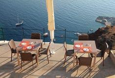 Alfresco cafe on terrace over sea coast, Santorini, Greece Stock Image