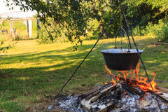 Alfresco cooking. Cooking outdoors over an open fire with a traditional Hungarian cooking pot Stock Photography