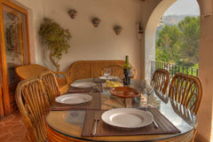 Alfresco Dining. A table located on a veranda with plates and wine Stock Photos
