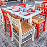 Alfresco restaurant with white and red table and chairs, Greece Stock Images
