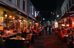 Alfreskomålning som äter middag, nattetid i den gamla Townnen, Bucharest som är romani Arkivbilder