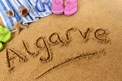 Algarve beach Portugal. The word Algarve written on a sandy beach, with beach towel, starfish and flip flops Stock Images