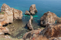 Algarve coast, Portugal. Rocks in the shoreline and blue water Stock Image