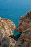 Algarve coast, Portugal. Rocks in the shoreline and blue water Royalty Free Stock Photography