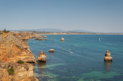 Algarve coast, Portugal. Rocks in the shoreline and blue water Royalty Free Stock Photos