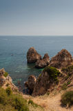 Algarve coast, Portugal. Rocks in the shoreline and blue water Royalty Free Stock Photo